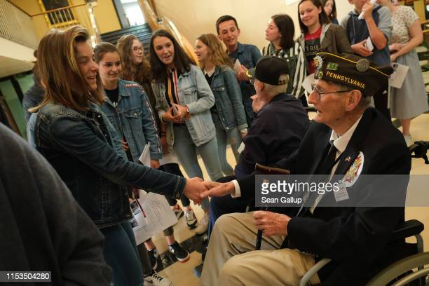 American DDay veterans including Walter Hurd who served in the 82nd Airborne Division receive a warm farewell from local high school students after...