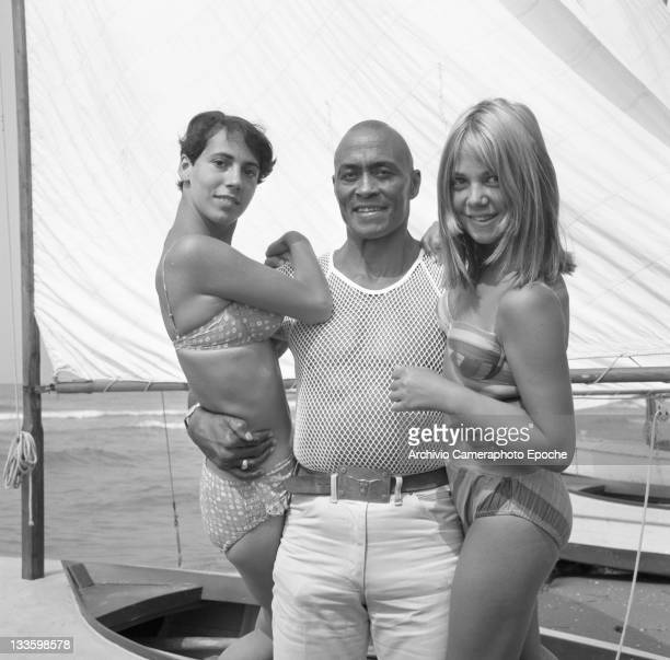 American decathlete and actor Woody Strode portrayed while hugging two girl fans Venice Lido 1967