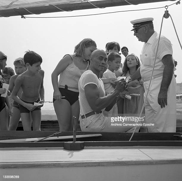 American decathlete and actor Woody Strode sitting on a boat on the seashore portrayed while signing autographs Lido Venice 1967
