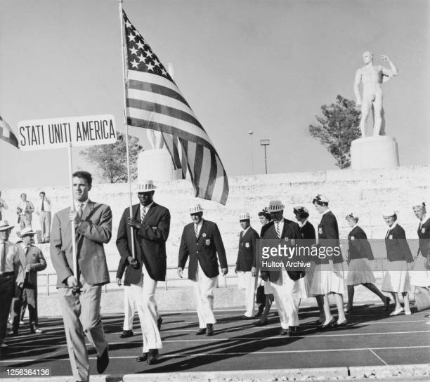 American decathlete Rafer Johnson is the flag bearer leading the United States Olympic team as they leave the Stadium of the Marbles on their way to...
