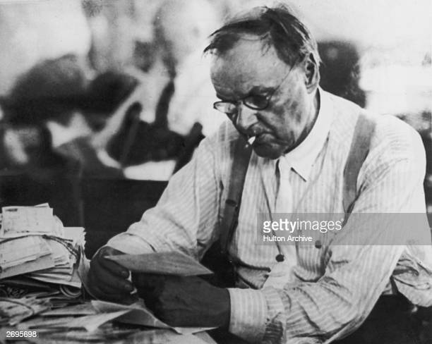 American defense attorney Clarence Darrow smokes a cigarette between his teeth while reading through a pile of mail during the Scopes 'monkey trial'...