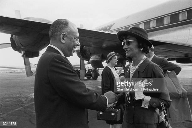 American department store executive Stanley Marcus holds hands and says goodbye to French fashion designer Coco Chanel at the airport after her visit...