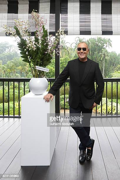 American designer, Michael Kors poses for a photo with the Dendrobium Michael Kors, an orchid that was named after him at the National Orchid Garden...
