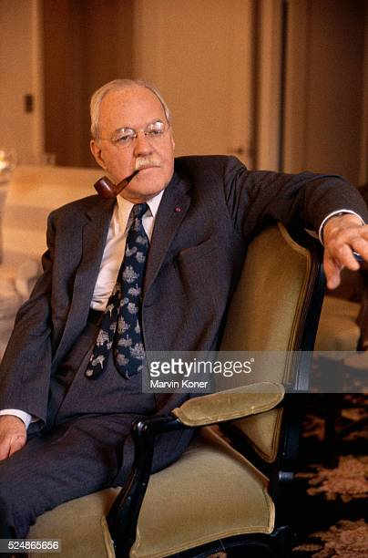 CIA director Allen Welsh Dulles sitting in a chair and smoking a pipe
