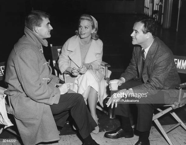 American director Blake Edwards American actor Lee Remick and American actor Jack Lemmon discuss a scene as they sit in canvas director's chairs and...
