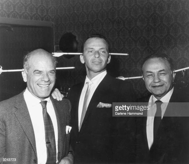 American director Frank Capra and American actors Frank Sinatra and Edward G Robinson wear gag arrows at a party for Capra's film 'A Hole In The...