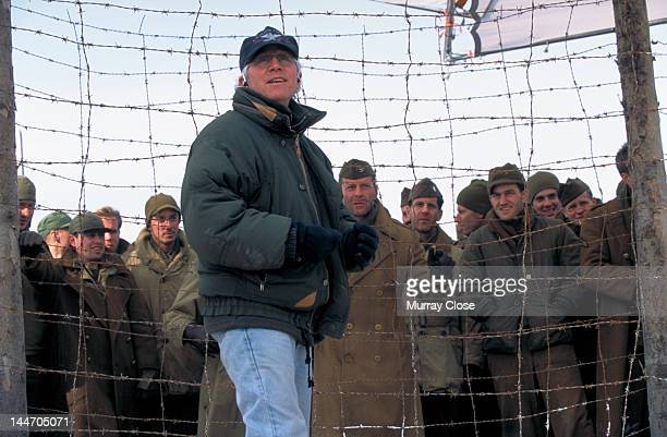 American director Gregory Hoblit on the set of his film 'Hart's War', 2002. Actor Bruce Willis is amongst the men standing behind the fence.