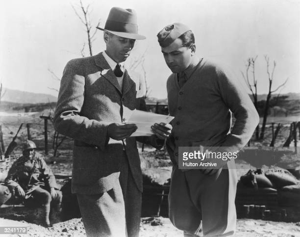 American director Howard Hawks talks with American actor Richard Barthelmess dressed as a World War I soldier on the set of his film 'The Dawn Patrol'