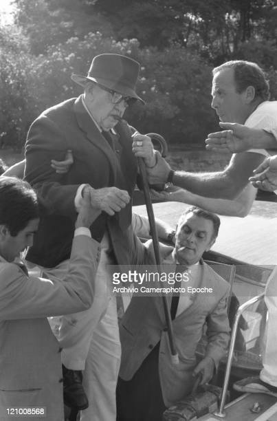 American director John Ford wearing a suit a tie and a hat holding a walking stick and smoking a cigar portrayed while helped by others to get out of...
