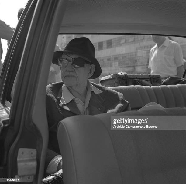 American director John Ford wearing a suit a tie and a hat portrayed on a car in Lido Venice 1971