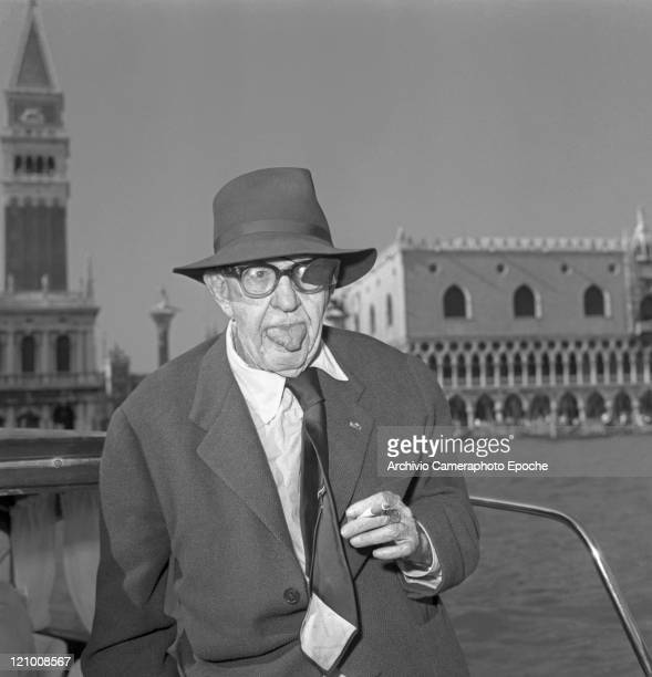 American director John Ford wearing a suit a tie and a hat portrayed inside a water taxi while smoking a cigarette and poking his tongue St Mark's...