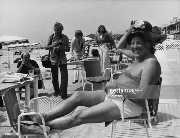 American director Joseph Losey wearing an elaborate hat on the beach in Cannes France during the Cannes Film Festival 12th May 1973 He is presenting...