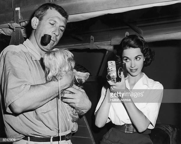 American director Richard Brooks smokes a pipe and holds actor Dana Wynters's small dog a miniature Skye terrier while Wynter points a handheld movie...