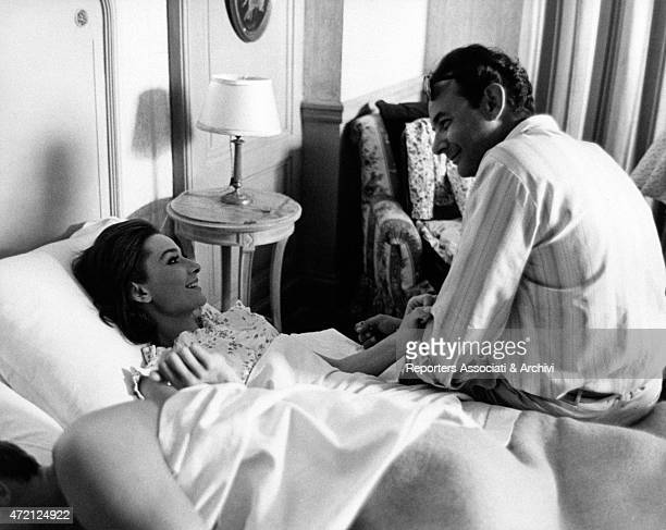 American director Stanley Donen sit on the side of a bed talk affectionately with Audrey Hepburn under the blankets in a dressing gown during the...