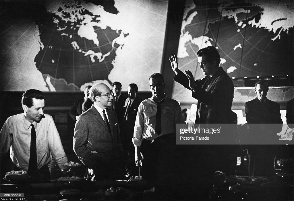 American director Stanley Kubrick (1928 - 1999, gesturing, right) directs British comic actor Peter Sellers (1925 - 1980, second from left) on the Pentagon War Room set, during filming of the 1964 satirical comedy, 'Dr. Strangelove or: How I Learned to Stop Worrying and Love the Bomb', at Shepperton Studios, Surrey, circa 1963. Looking on (centre) is American actor George C. Scott (1927 - 1999). Sellers is in costume for the role of President Merkin Muffley, one of three characters he portrays in the film.