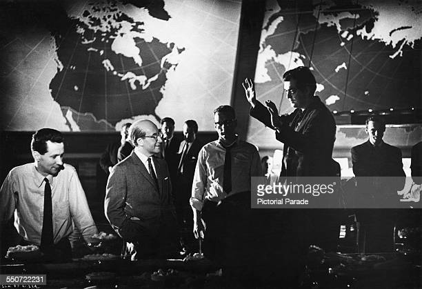 American director Stanley Kubrick directs British comic actor Peter Sellers on the Pentagon War Room set, during filming of the 1964 satirical...
