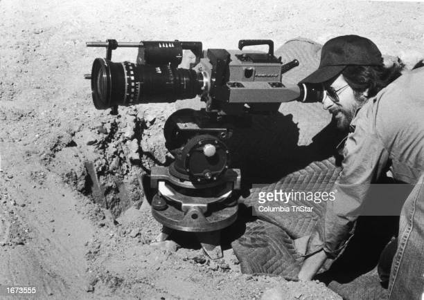 American director Steven Spielberg crouches to look in the camera lens as he directs a film on location 1980