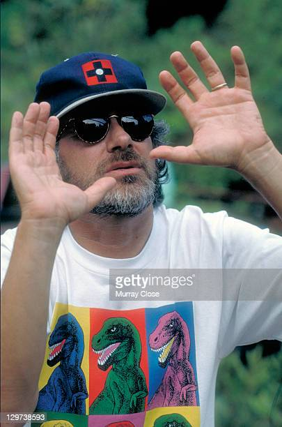 American director Steven Spielberg on the set of the film 'Jurassic Park', 1993. He is wearing a Warhol-inspired dinosaur t-shirt.