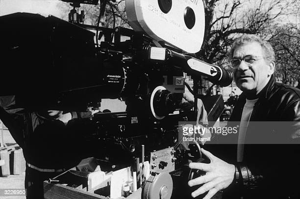 American director Sydney Pollack stands outside looking into a movie camera on the set of his film 'Sabrina'