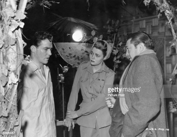 American director Vincent Sherman coaches actors Richard Todd and Patricia Neal through a dramatic scene in the Warner Brothers film 'The Hasty...