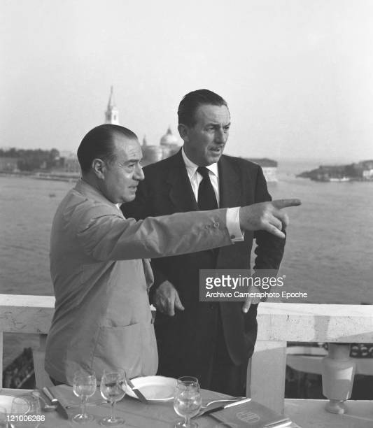 American director Walt Disney wearing a suit and a tie portrayed on the Danieli's terrace restaurant with a man St Mark's basin in the background...