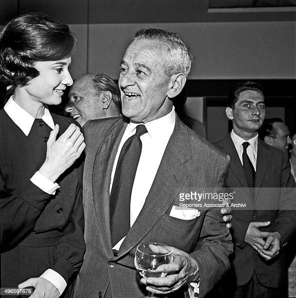 American director William Wyler hugging with enthusiasm British actress Audrey Hepburn at the cocktail in Cinecittà for the inauguration of the...
