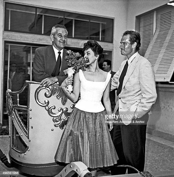 American director William Wyler posing on a chariot with American actor Charlton Heston and his wife and American actress Lydia Clarke at the...