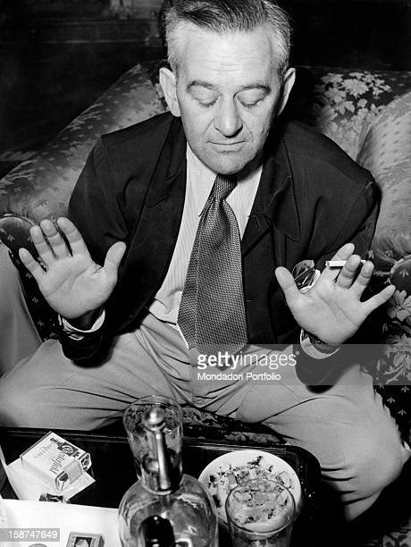 American director William Wyler sitting in an armchair and smoking a cigarette at the Grand Hotel in Rome during the press conference for the...