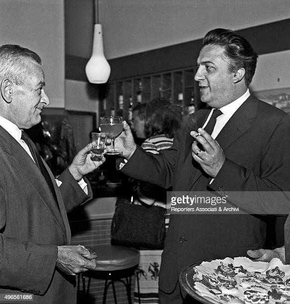 American director William Wyler toasting with Italian director Federico Fellini at the cocktail in Cinecittà for the inauguration of the shooting of...