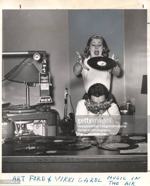 American disc jockey Art Ford of WNEW Radio holds out his hands to catch a record dropped by singer Vikki Carol New York New York mid 1950s Photo by...