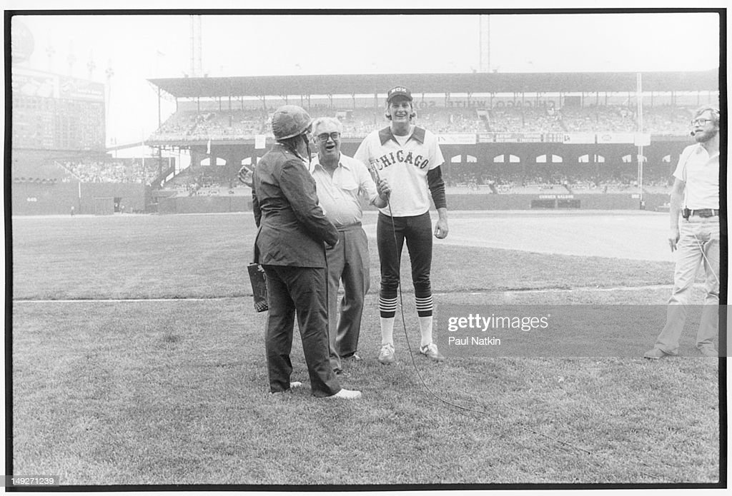 American disc jockey (from WLUP radio, 'The Loop') Steve Dahl (left, in helmet) speaks with Chicago White Sox announcer Harry Caray (born Harry Carabina, 1914 - 1998) on the field during an anti-disco promotion at Comiskey Park, Chicago, Illinois, July 12, 1979. The event, hosted by Dahl and held between games of a doubleheader between the Chicago White Sox and the Detroit Tigers, allowed fans to attend the games for 98 cents along with an unwanted record and, following the detonation of those records, eventually resulted in the White Sox forfeiture of the second game due to unsafe playing conditions when fans stormed the field causing serious damage to the venue and playing surface.