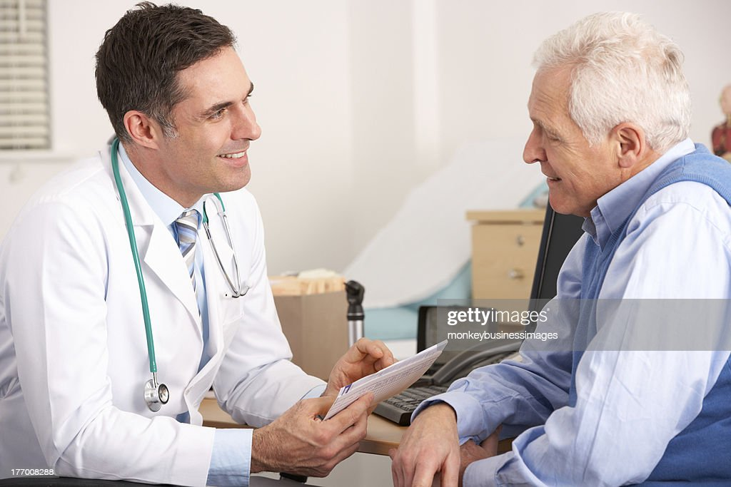 American doctor talking to senior man in surgery : Stock Photo