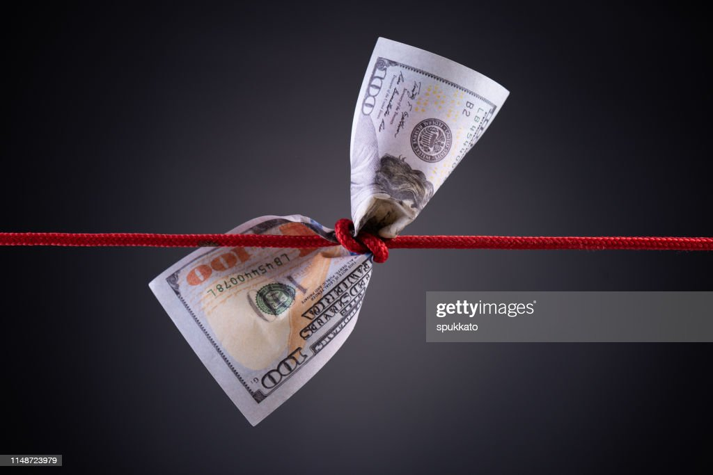 American dollar tied up in red rope knot on dark background with copy space. business finances, savings and bankruptcy concept. : Stock Photo