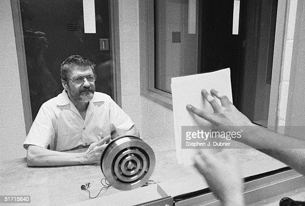 **EXCLUSIVE** American domestic terrorist luddite and mathematics teacher Ted Kaczynski looks at a document pressed to the dividing glass by an...