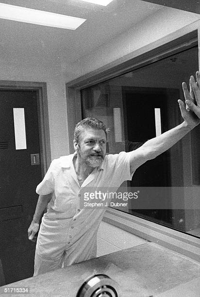 **EXCLUSIVE** American domestic terrorist luddite and mathematics teacher Ted Kaczynski presses his hand against a reporter's through the dividing...