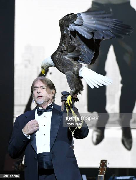 American Eagle Foundation Founder and President Al Louis Cecere prepares to fly a bald eagle named Challenger as the American national anthem is...