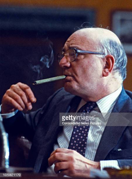 American economist Chairman of the Federal Reserve Paul Volcker smokes a cigar during his testimony before the US Senate Committee on Banking Housing...