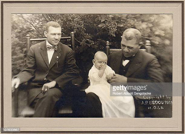 Educator Booker T Washington holds his grandson on his lap while sitting next to his son ca 1915