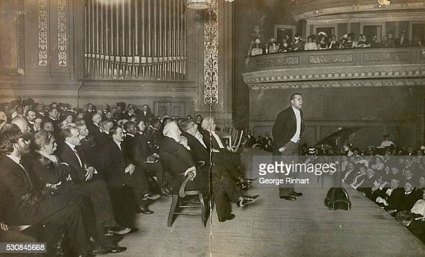 Mark Twain seated in the front row at far right listening to Booker T Washington as he speaks at Carnegie Hall for his Tuskegee Institute Silver...