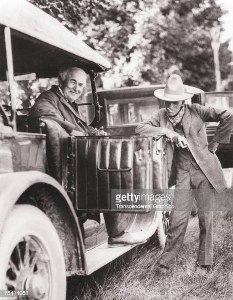 American engineer and inventor Thomas Alva Edison smiles as he sits in a car and poses with his friend and fellow industry tycoon Henry Ford who...