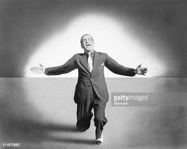 American entertainer Al Jolson sings with his arms outstretched and knees bent