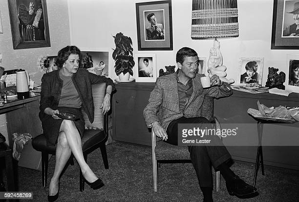American entertainer Dick van Dyke and an unidentified woman sit in the photographers office 1960s Dyke holds a mug the woman holds an ashtray