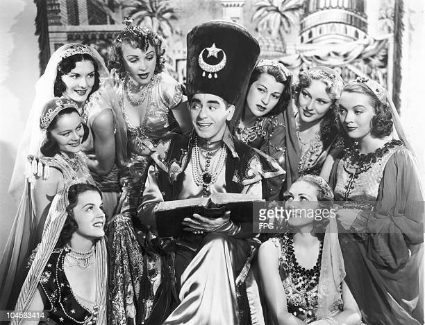 American entertainer Eddie Cantor surrounded by beautiful 20th Century Fox stock players between scenes of his new musical spectacle 'Ali Baba goes...