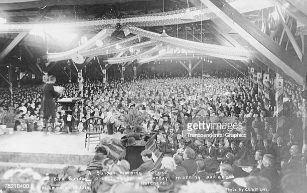 American evangelical preacher Billy Sunday delivers a sermon to some 6000 attendees at a revival meeting, Bloomington, Illinois, late 1907 or early...