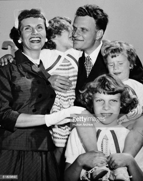 American evangelist Billy Graham embraces his family upon his return from his 'Crusade for Christ' tour New York New York mid 1950s Clockwise from...