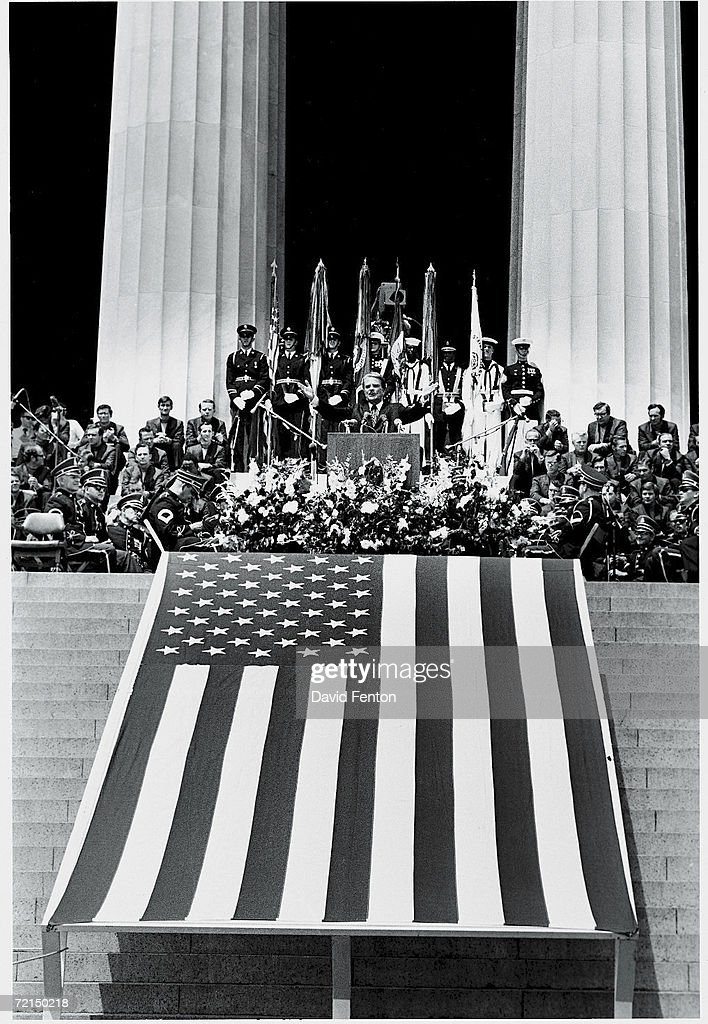 American evangelist Billy Graham spreads his arms in a wide gesture as he speaks to a crowd from a podium above a giant American flag on the steps of the Lincoln Memorial while surrounded by uniformed members of the armed forces duting 'Honro America Day,' Washington, DC, July 4, 1970.