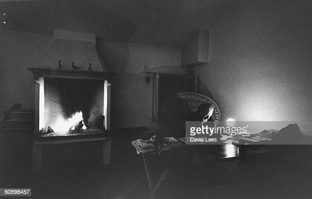 American expatriate poet Ezra Pound sitting at desk in darkened room writing by candle and fire light