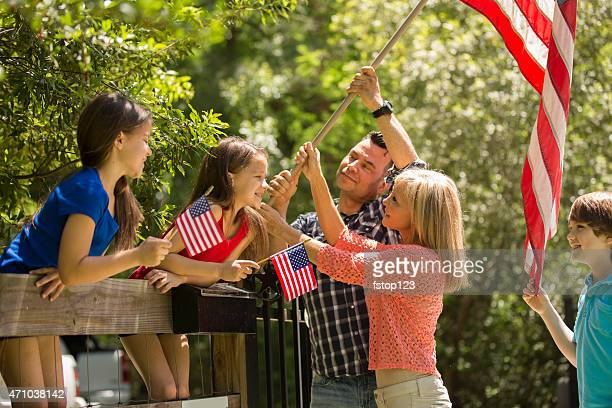 American family puts up USA flag on home fence. Outdoors.