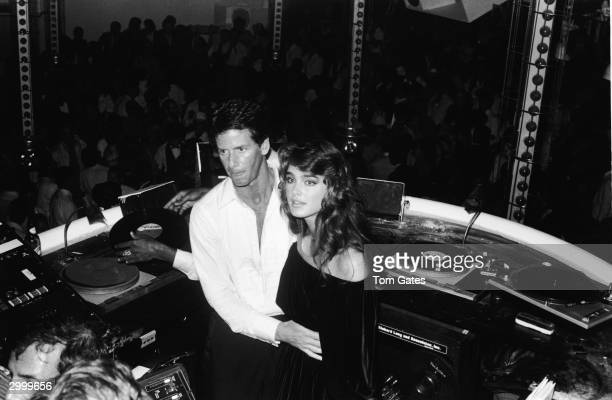 American fashion designer Calvin Klein and model and actor Brooke Shields stand in the DJ booth at the reopening of Studio 54 nightclub New York City...