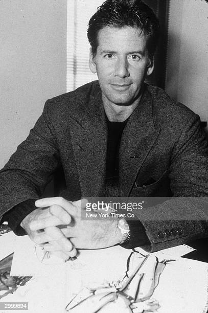 American fashion designer Calvin Klein sits at his desk with copies of his designs New York City April 10 1985